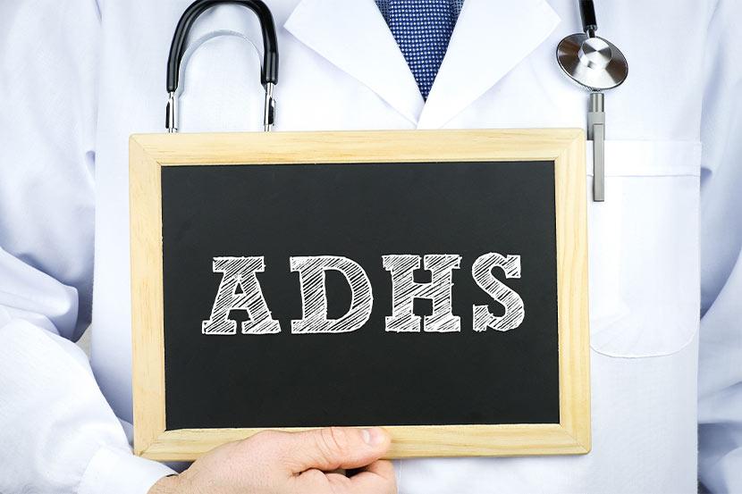 ADHS-Experte und Facharzt hält eine Tafel hoch.