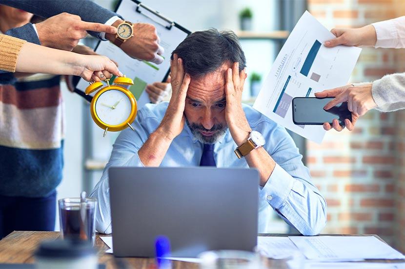 Geschäftsmann im Büro ist überfordert von zu vielen Tätigkeiten.