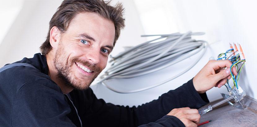 Profi-Elektrotechniker beim Einbau einer Steckdose in einer Wohnung.