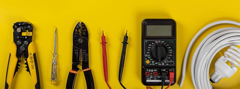 Kabel, Kabelzange, Schraubenzieher, Energiesparlampe und Strommessgerät.
