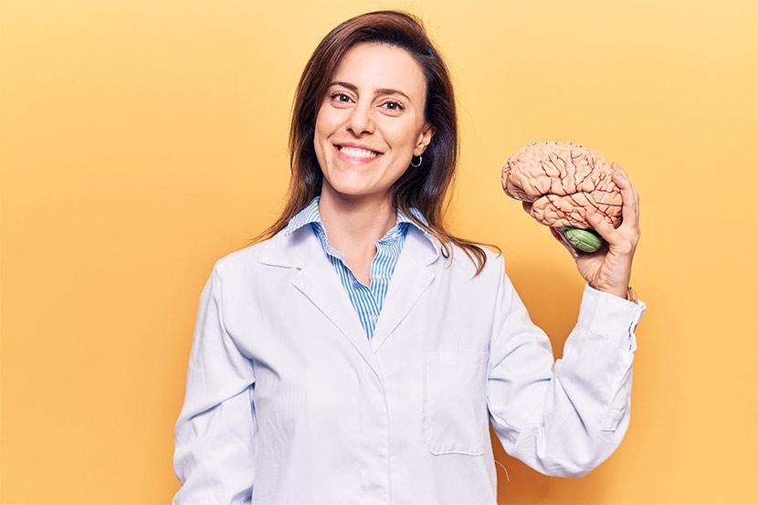 Fachärztin für Neurologie mit Hirnmodell.