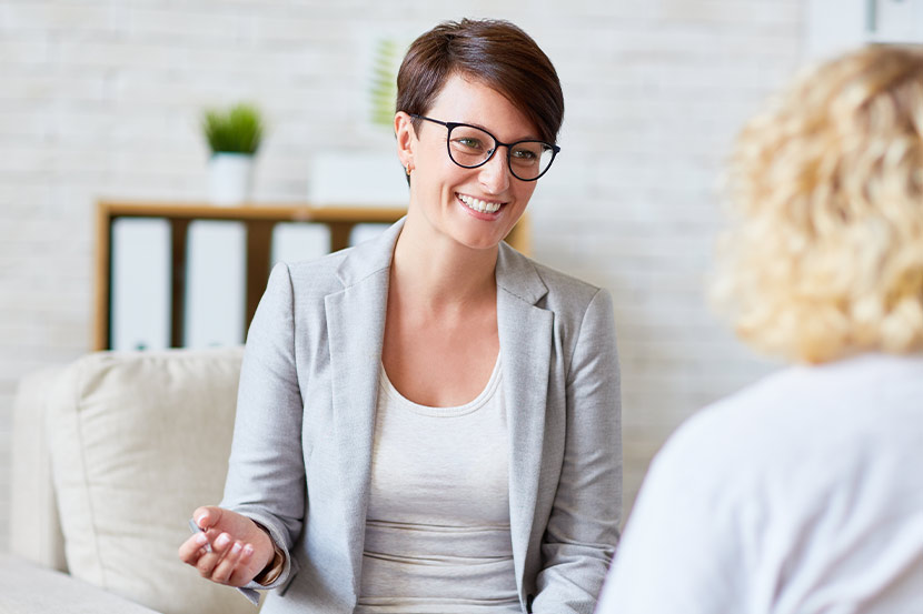 Psychologin in Gespräch mit Patient in ihrer Praxis.