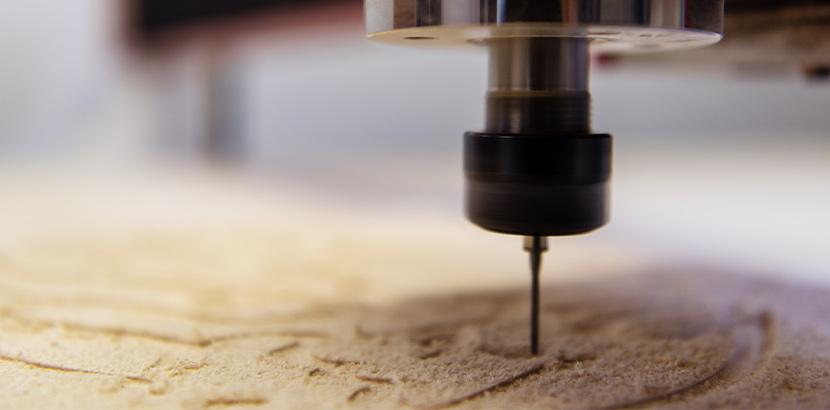 Eine CNC-Fräse die filigrane Details in ein Holzstöck fräst.