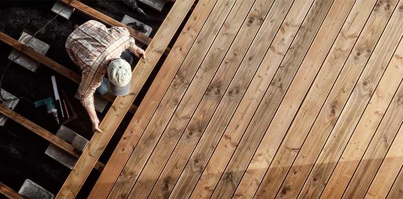 Meistertischler beim Verlegen von Holzbrettern als Bodenbelag für eine Holzterrasse.