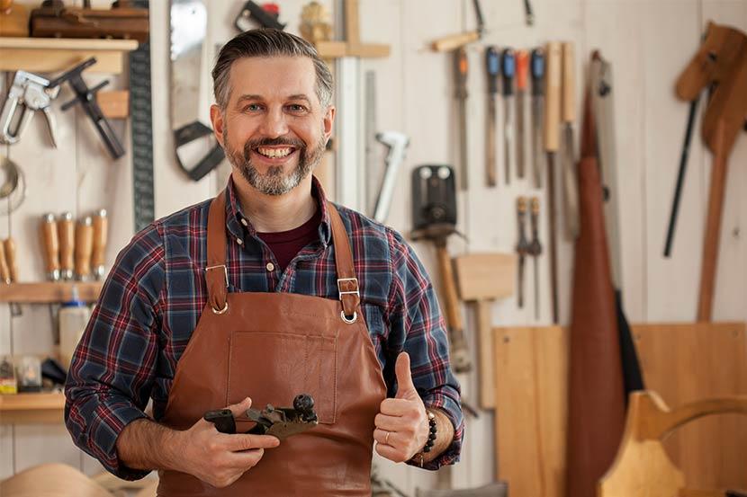 Freundlicher Tischler lächelt in seiner Werkstatt bei der Anfertigung von Möbeln.