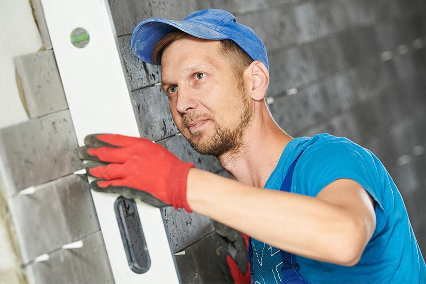 Handwerker bei Kontrolle und Verfugen von Wandfliesen auf Baustelle.
