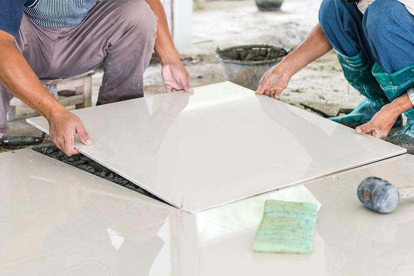 Zwei Meisterfliesenleger bei der Verfliesung mit einer Bodenplatte aus Keramik im Großformat.