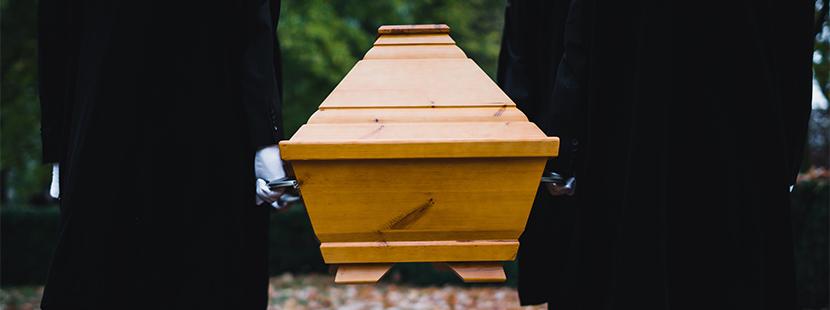 Sargträger betten Verstorbenen bei Beerdigung zur letzten Ruhe. Ablauf von Erdbestattung.