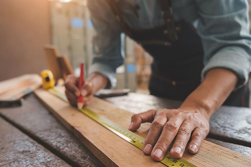 Tischlergeselle bei der Arbeit in der Holz-Werkstatt.