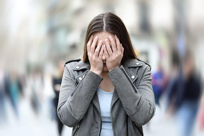 Frau auf öffentlichem Platz leidet an starker Angst.