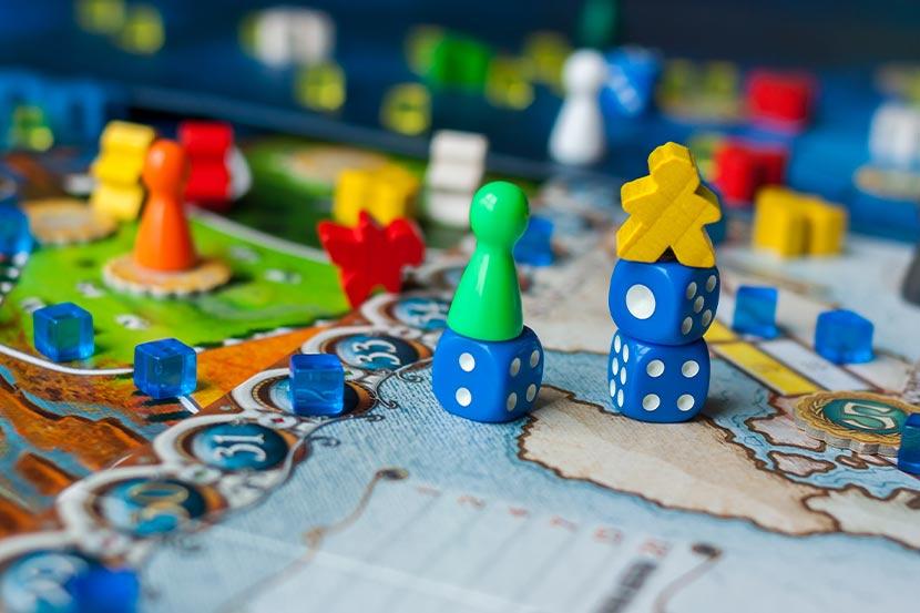 Brettspiel mit Karten, Würfeln und Figuren auf einem Tisch.