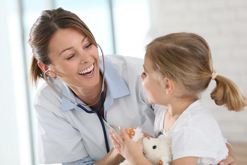 Junges Mädchen und lächelnde Ärztin bei Untersuchung.