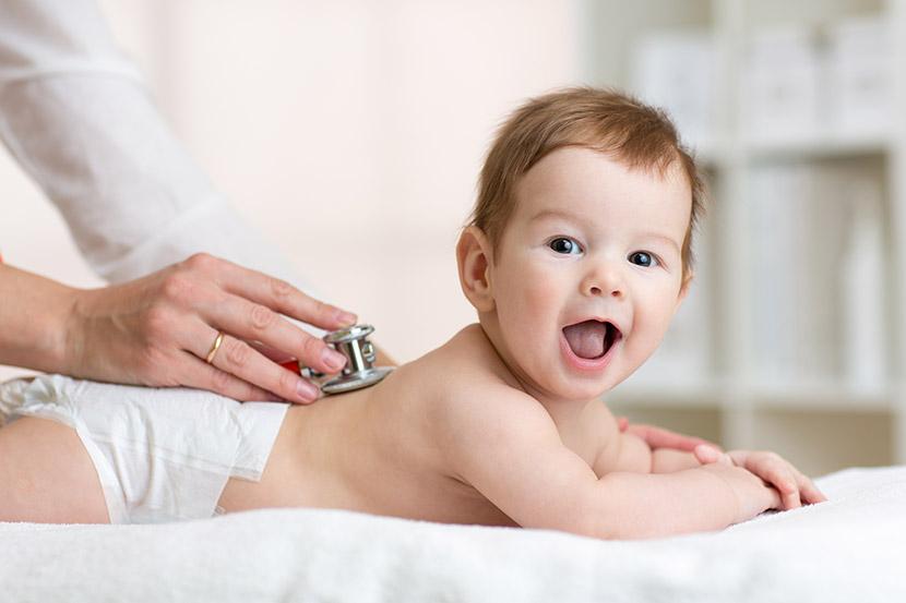 Baby lächelt und fühlt sich wohl bei Arzttermin.