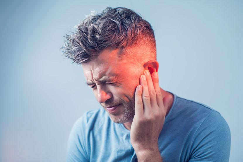 Mann mit Mittelohrentzündung hält sich Hand an die Schläfe.