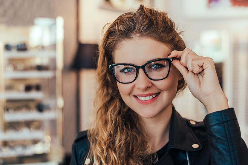 Junge Frau probiert neue Brille bei Optikermeister an.