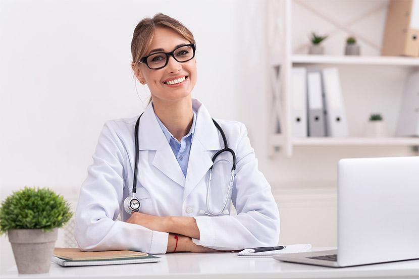 Arzt für Allgemeinmedizin in Behandlungszimmer gibt Patient Informationen und Tipps.