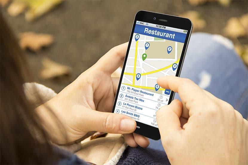 Junge Frau, die via Smartphone eine lokale Suchanfrage nach einem Restaurant in ihrer Nähe absetzt. Angezeigt werden jene Lokale, die in Local SEO investiert haben,