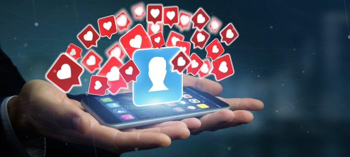 Hände, die ein Tablet halten, aus dem ein von Herzchen umgebener Avatar aufsteigt,. Wie wichtig ist Social Media wirklich?