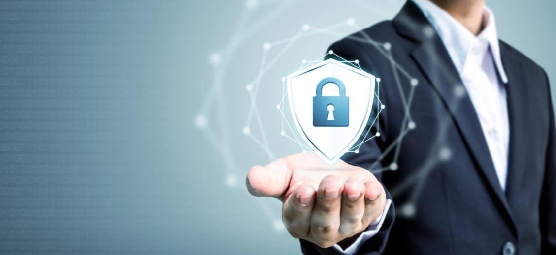 Geschäftsmann im Anzug vor blauem Hintergrund, der ein Sicherheitszeichen in der geöffneten Handfläche hält.