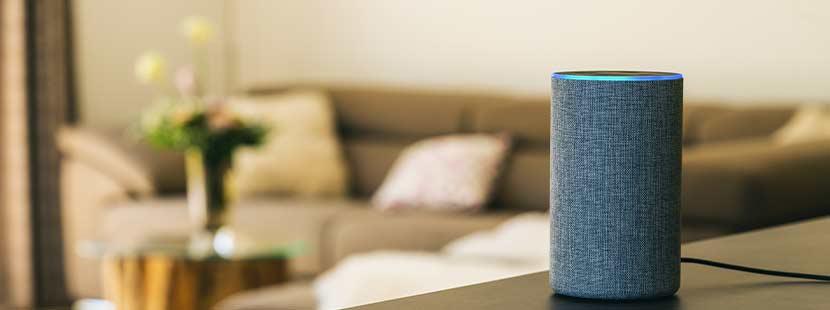 Smart Speaker, der in einem Wohnzimmer auf dem Tisch steht und auf Voice Search optimiert ist.