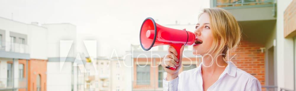 Junge blonde Frau. die mit einem Megafon auf ihrem Blakon steht und Werbung für ihre Website macht,