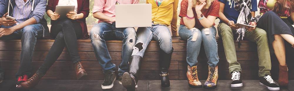 Gruppe von jungen Menschen, die mit Laptop und Smartphone im Internet surfen.