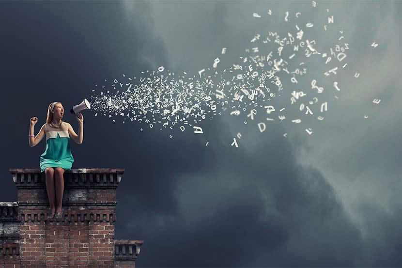 Junge Frau, die von einem Dach aus Suchanfragen per Megafon stellt.