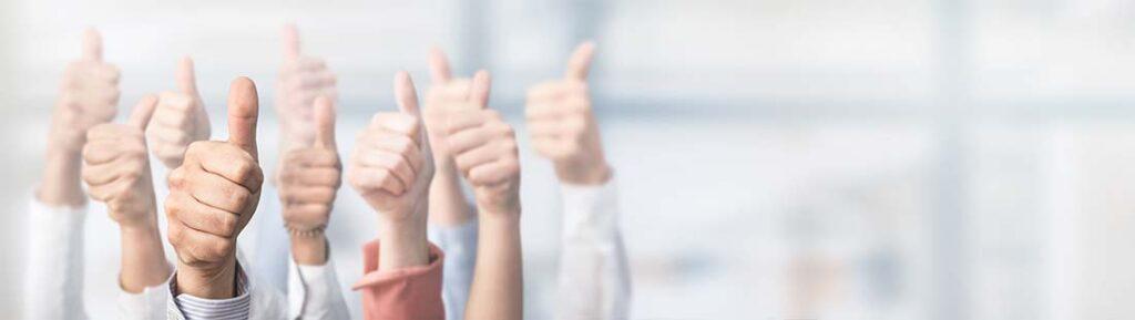 Mehrere Geschäftsleute, die den Daumen nach oben halten, um die Inbound Marketing Strategie zu feiern.