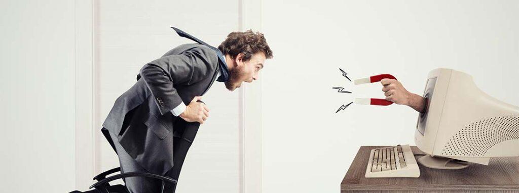 Junger Mann, der von einem Magneten durch den Computer Bildschirm gesaugt wird. Inbound Marketing.