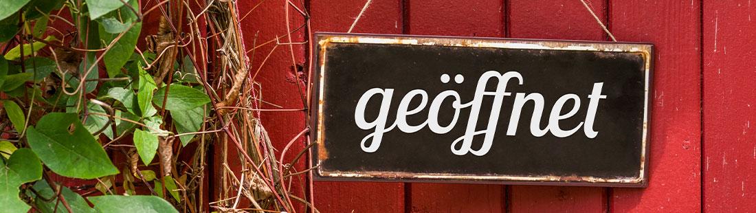 """Schild, auf dem """"geöffnet"""" steht, und das einer rot gestrichenen Ladentür hängt. Lokal besser gefunden werden."""