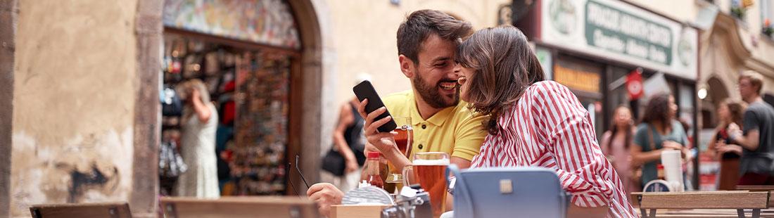 Junges glückliches Pärchen in einem Café, die mit dem Handy eine lokale Suche über Google absetzen.