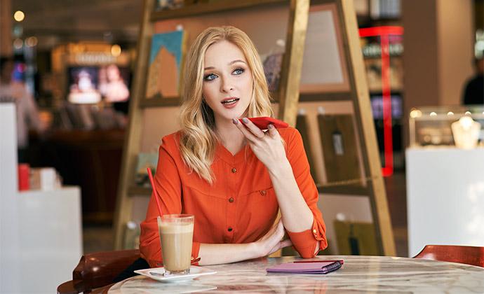 Junge blonde Frau stellt ihrem Smartphone Fragen um Inhalte über Suchmaschinen abzurufen.