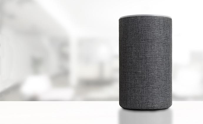 Amazon Smart Speaker, der in einem Wohnzimmer auf dem Tisch steht und Antworten sowie Ergebnisse liefert.