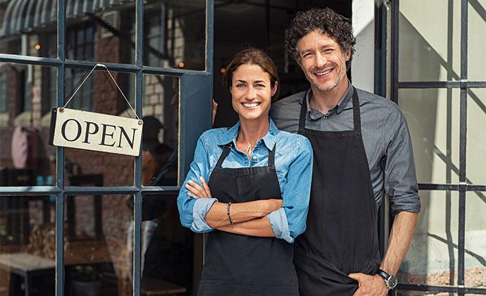 Mann und Frau optimieren ihre Firmen Website für Keywords um Sprachsuche als Marketing Tool zu verwenden.