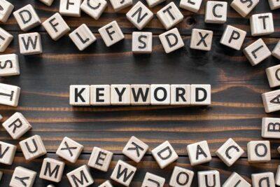 Der Begriff Keyword versteckt unter Buchstabenwürfeln auf einem Tisch aus Holz.