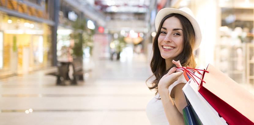 Junge Frau kauft Produkte in einem Geschäft ein.
