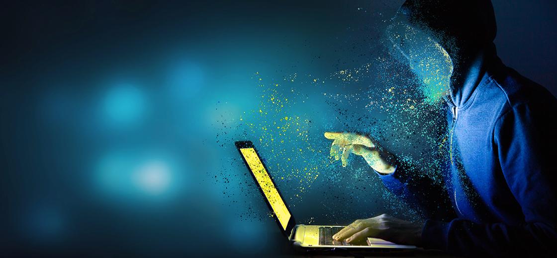 Hacker mit Laptop als Symbol für Cyber Security